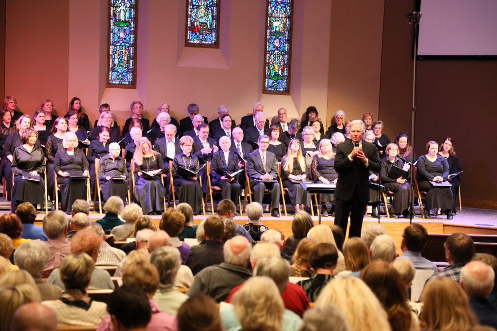 Maestro Jere Lantz speaks about the history of a piece at one of Minnetonka Choral Society's live music concerts in the Twin Cities.